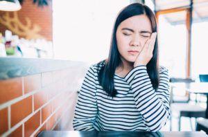 Mulher sente dor por conta da sensibilidade nos dentes